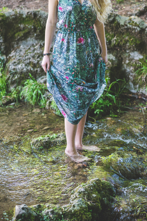 Close up on the legs of young woman wearing floral skirt barefoot in the river