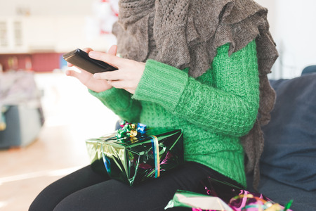Close up on the hand of young handsome woman tapping on the screen of a smart phone sitting on the sofa with a wrapping gift leaning on her knee Stockfoto