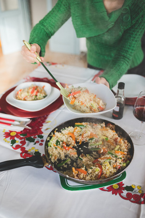 Close up on the hand of young handsome girl serving rice and vegetables from a pan to a plate using perforated spoon for chrismas meal