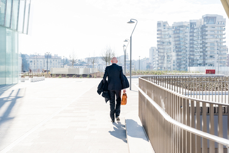 Back view of middle-age businessman holding briefcase walking outdoor in back light Stockfoto