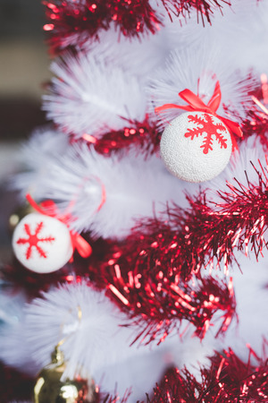 Close up on white chrismas tree decorated with colorful little ball and red decoration