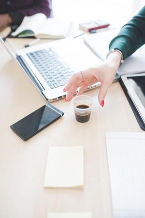Close up on the hand of businesswoman holding a cup of coffee on a desk with technological devices