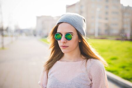 Portrait of young beautiful caucasian woman outdoor in city back light wearing mirrored vintage sunglasses