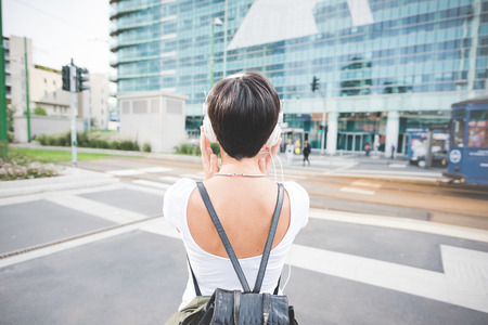 Half length rear view of a caucasian woman with backpack listening music with headphones - music, relax concept