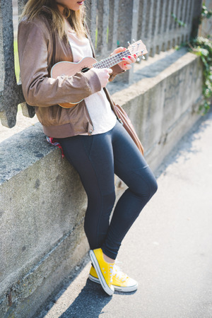 Close up on young woman playing ukulele - musician, composer, artist concept Stockfoto