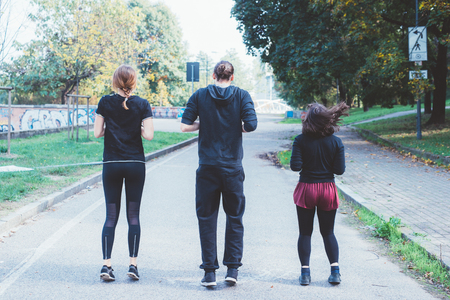 Three women and man runners from back running outdoor in city park in autmun - runners, training, athlete concept Stockfoto