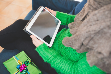 Close up on the hand of young handsome woman tapping on the screen of a tablet sitting on the sofa, gift place on her side- technology, communication, social network concept Stockfoto