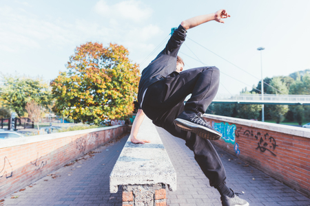 Young beautiful caucasian man doing parkour outdoor in the city in autumn - stunt, acrobat, trick concept Stockfoto