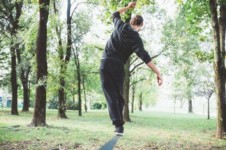 Man balancing a tightrope or slackline outdoor in a city park in autumn - slacklining, balance, training concept