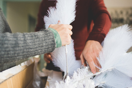 Close up on hands of couple of young handsome caucasian man and woman unpacking christmas tree, looking downward, concentrate - christmas, holiday, winter concept