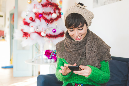 Young handsome caucasian brown hair woman sitting on sofa, present on her knee, holding smartphone, looking downward the screen, smiling - christmas, technology, social network, communication concept