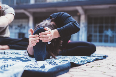 Close up on the hand of young woman stretching outdoor in the city, holding her feet - training, stretching, sportive concept