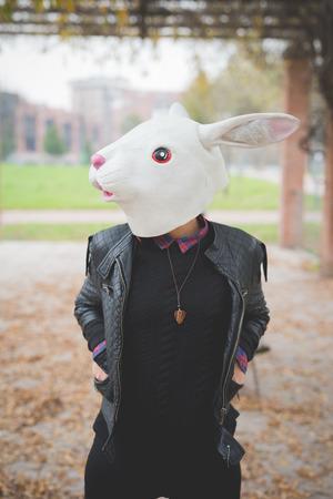 Woman wearing rabbit mask outdoor in autumn park - carnival, halloween, strange concept