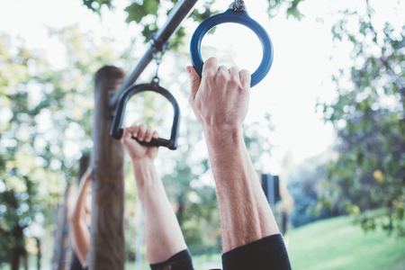 Close up on the hand of young man training in a park using rings - gymnast, training, sportive concept
