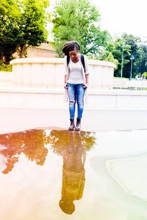 Young black woman outdoor in the city reflected on a puddle outdoor in the city Stockfoto