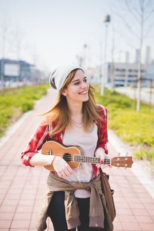 young beautiful blonde hipster woman in the city with ukulele