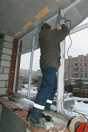 house worker: The builded house. Worker establishing window frames.