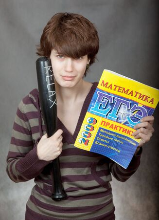 colleen: Girl with a textbook in mathematics and a baseball bat. Stock Photo