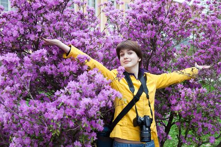 colleen: Funny girl in a yellow jacket with a camera. Stock Photo