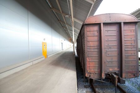 A railway freight wagon standing at the platform of modern warehouse Stock Photo - 7868500