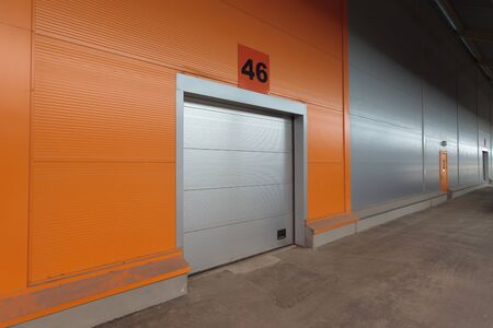Modern warehouse's gate number 46 in orange wall. Stock Photo - 12943643