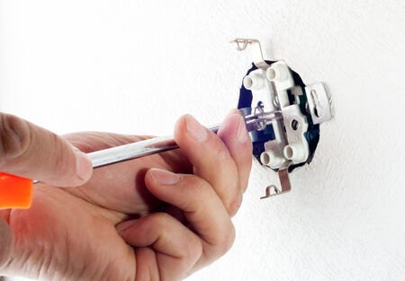 outlet: closeup of electrician hands installing wall socket