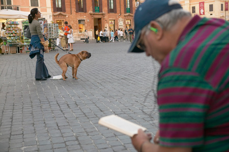 shit: Piazza della Repubblica (Republic Square). Rome. Italy. Woman with dog. The dog is defecating