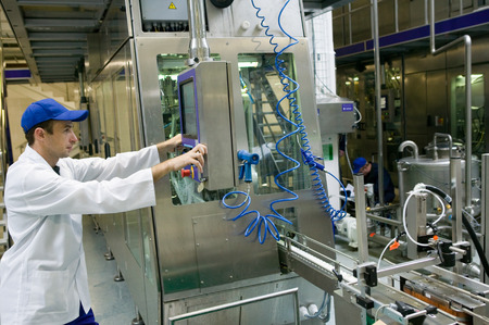 bottling line: The line for bottling milk. Worker with the administrator terminal.