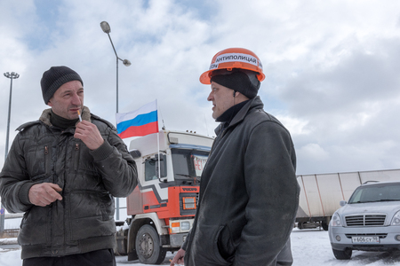 platon: Saint Petersburg, Russia. 23 February 2016:  Truck drivers and their supporters gather to protest against the new road payment system, named Platon. Truckers camp in the parking lot at the shopping center MEGA Dybenko in St. Petersburg. The word on th