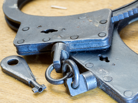 manacle: Handcuffs, Security concept on wooden background Stock Photo