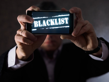 The man is holding a smartphone in his hands, facing the viewers with the inscription Blacklist on the screen. Reklamní fotografie