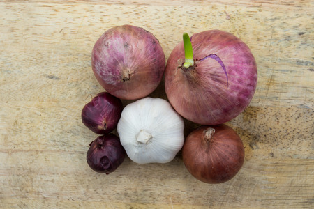 chopping board: Onions and garlic over chopping board Stock Photo
