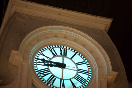 Nighttime view of clock tower with backlit face