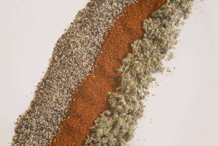 Macro shot of black pepper, paprika, and sage on a white background