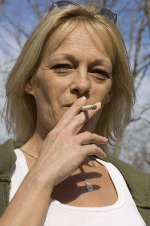 Woman smoking a cigarette in the outdoors on a sunny day