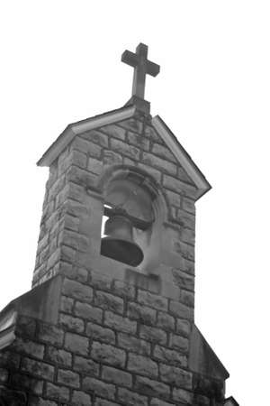 Black and white view of an older church steeple with bell. Looks like an old west style church steeple Stock Photo