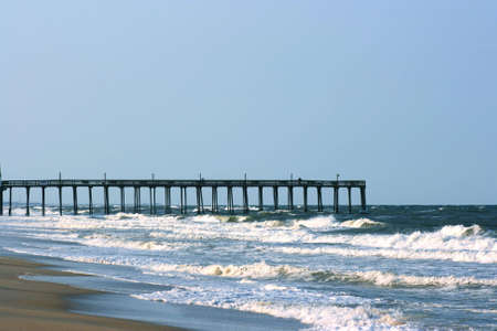 Pier jutting out into the ocean from the beach. Stock Photo
