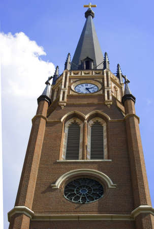 reminding: Church tower with cross on top and clock. Reminding parishoners of time to worship with clock on church steeple. Stock Photo