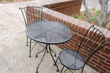 Table and chairs for an outdoor cafe on a pebble sidewalk Stock Photo