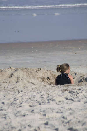 Female child playing in a hole in the sand at the beach. Oceanside fun by digging a hole in the sand Stock Photo - 2802801
