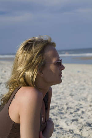 An adult female sitting on the beach looking off into the ocean. Staring into the waves of the Atlantic Stock Photo