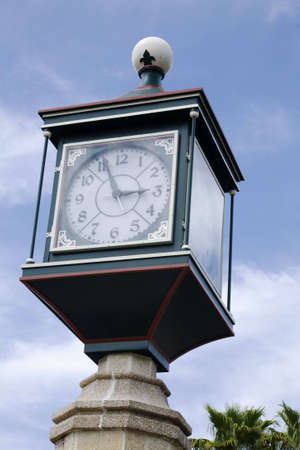 Ornate clock mounted on a concrete post in a public square
