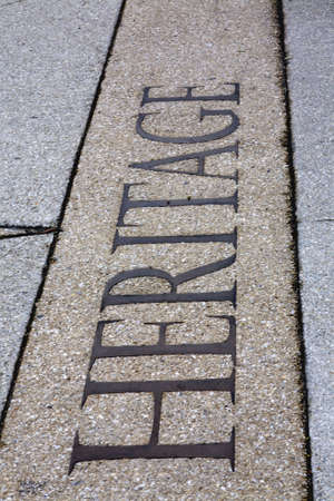 The word heritage inscribed into a pebble sidewalk Stock fotó