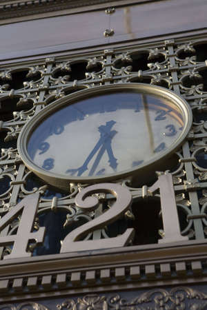 Golden clock in ornate metal work above a street address label.  Stock Photo