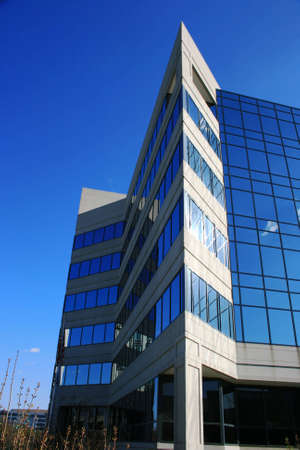 Office building with blue shiny glass, and a triangular point to the front.