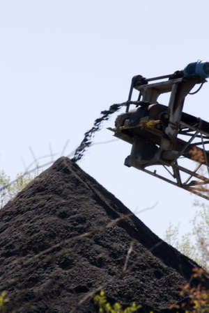 Moving dirt through an automated conveyor belt system. Conceptualization of the ease of digging up the natural order and discarding it to a pile of dirt. Motion blur of dirt exiting the conveyer. Stock Photo