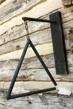 Nostalgic western style dinner bell. Triangle mounted to split wood wall. Stock Photo