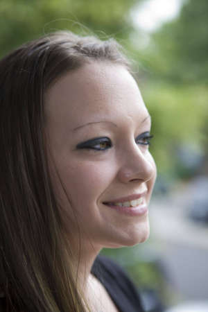 smiing: Side view of a young woman smiling as she looks in the distance