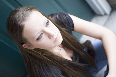 Young woman sitting patiently on a doorstep in thought, waiting for something to arrive.  Imagens