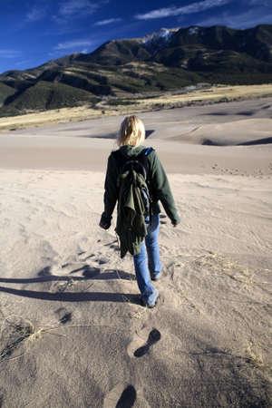 outoors: Woman walking away across a sandy landscape